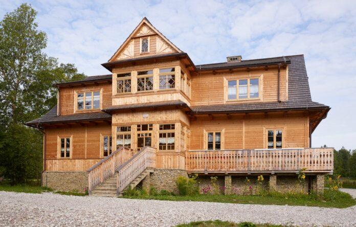 drewniany budynek kryty gontem z przeszklonym gankiem i werandą pośrodku, z wejściem po schodach i balkonem po lewej stronie